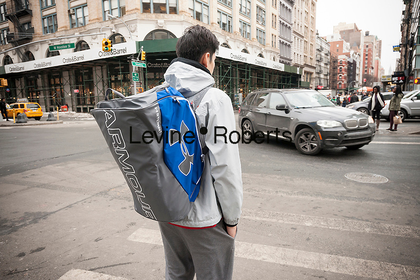 A pedestrian waits to cross Houston Street wearing an Under Armour branded backpack in Soho in New York on Friday, January 29, 2016.  (© Richard B. Levine)