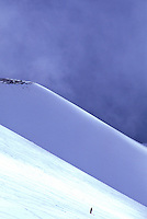 A snowboarder skis down a snow covered volcano on the slopes of Mauna Kea on the Big Island of Hawaii.