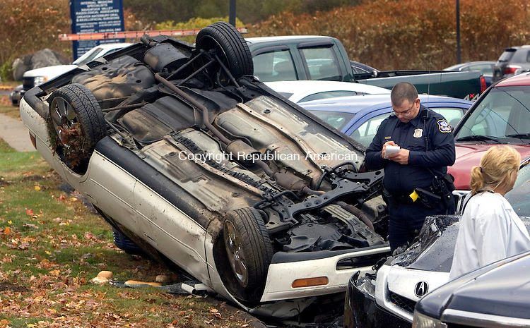 WATERBURY CT. 01 October 2013-110113SV08-A driver lost control in a curve and landed upside down on cars in a medical office building at 1389 West Main St. in Waterbury Friday. The driver suffered minor injuries.<br /> Steven Valenti Republican-American