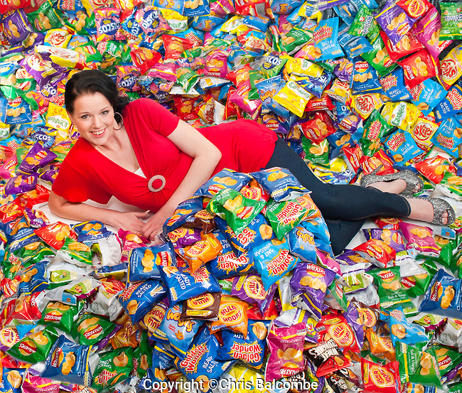 Feature for THE SUN Newspaper. Published 3rrd March 2014.<br /> <br /> 'I Lost 10 stone after giving up crisps'<br /> Pictured is slimmed-down EMMA DUCKWORTH,  with hundreds of packets of crisps of the type she used to eat.<br /> Pictured at home in Hampshire<br /> <br /> Pic: Chris Balcombe<br /> <br /> 07568 098176
