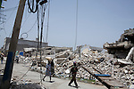 Pedestrians stroll past massive piles of earthquake rubble on July 8, 2010 in Port-au-Prince, Haiti.