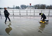 Nederland, Deventer, 14 jan 2011.Hoog water in de IJssel. In Deventer zijn zandzakken neergelegd om de huizen aan de ijsselkade te beschermen tegen het hoge water. Morgen stijgt het waterpeil nog..Voor kinderen is het allemaal plezier. Twee jongens vermaken zich met een speelgoed autootje. ..Foto (c)  Michiel Wijnbergh