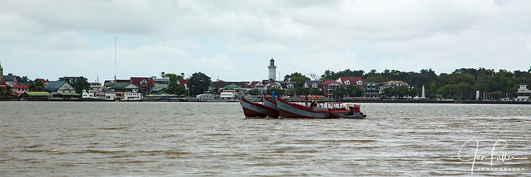 Boats on the Paramaribo River with the city and its tall clock tower on the Ministry of Finance building in the background.  Paramaribo, Suriname.