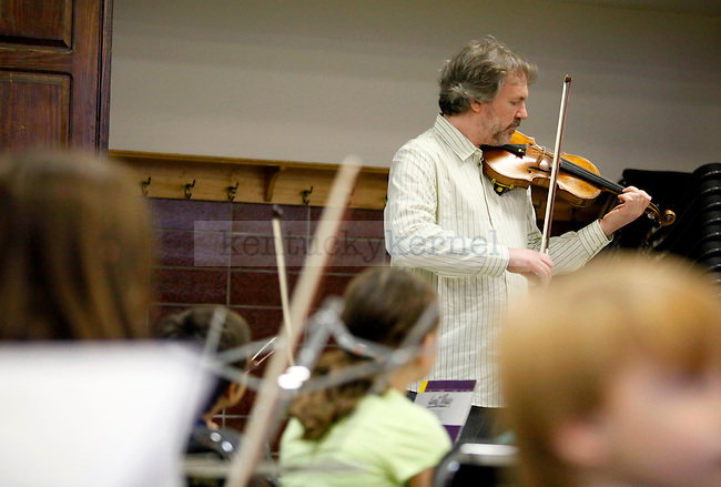 """Mark O'Connor plays """"Boild that Cabbage Down"""" with the students of the UK String Project class in the Band Room of the Fine Arts Building Saturday morning. O'Connor composed a ten book series called """"O'Connor Violin Method"""" to help students become well-rounded musicians. Photo by Zach Brake 