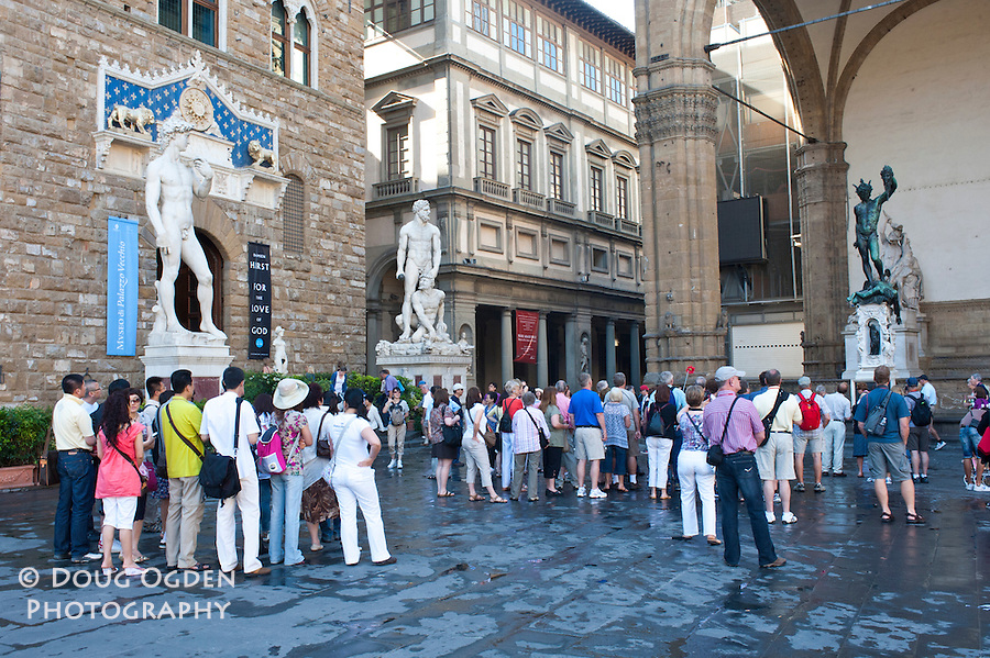 Tourists in the Piazza della Signoria, viewing (L to R) copy of David, Hercules and Cacus, and in the Loggia dei Lanzi Terrace, Perseus With the Head of Medusa, Florence, Italy