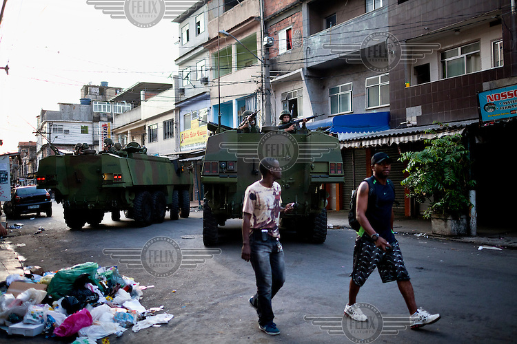 Armoured vehicles loaded with heavily armed military and special police block a street in Complexo da Mare near Rio de Janeiro's international airport. The favela consists of a complex of 16 communities, in the north zone of Rio de Janeiro. It is the largest complex of favelas, housing 130,000 residents. It is targeted for pacification as the city prepares for the 2014 World Cup and the 2016 Olympics.