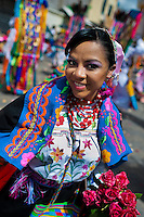 A dancer (danzante), holding flowers, takes part in the religious parade within the Corpus Christi festival in Pujilí, Ecuador, 10 June 2012. Every year in June, thousands of people gather in a small town of Pujili, high in the Andes, to celebrate the Catholic feast of Corpus Christi. Introduced originally during the Spanish conquest of South America, this celebration merges Catholic rituals of Holy Communion with the traditional Andean harvest and sun festivities (Inti, the Inca sun god). Women dancers perform wearing brightly colored costumes while men dancers wear chest ornaments and heavy elaborate headdresses adorned with mirrors, jewelry, or natural items (shells). Being a dancer in the Corpus Christi ceremonial parade (El Danzante) is considered an honour and a privilege by the indigenous people in Ecuador.