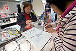Shoppers from China look at literature written in Mandarin about Arc Quest Co.'s Colantotte line of health and wellness products sold inside Matsuzakaya department store in the Ginza district of Tokyo, Japan on Tuesday 16 Nov. 2010..Photographer: Robert Gilhooly