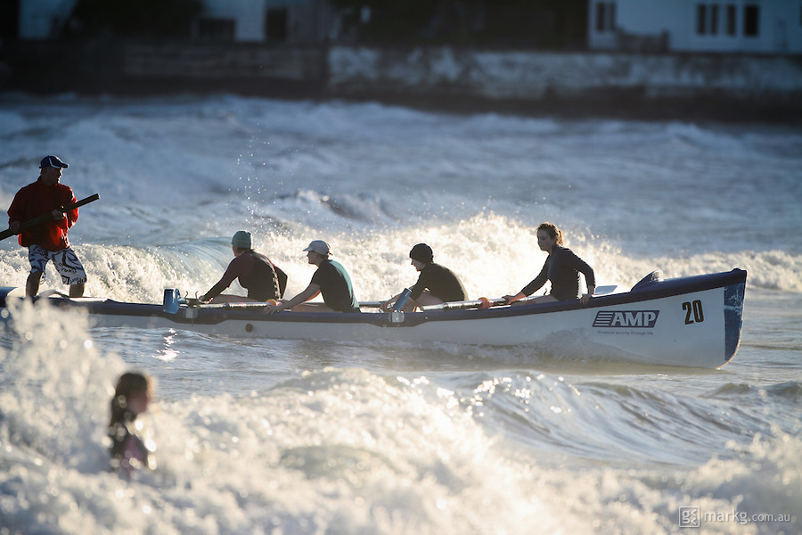 The Lyall Bay SLSC female boat crew catches a wave into shore