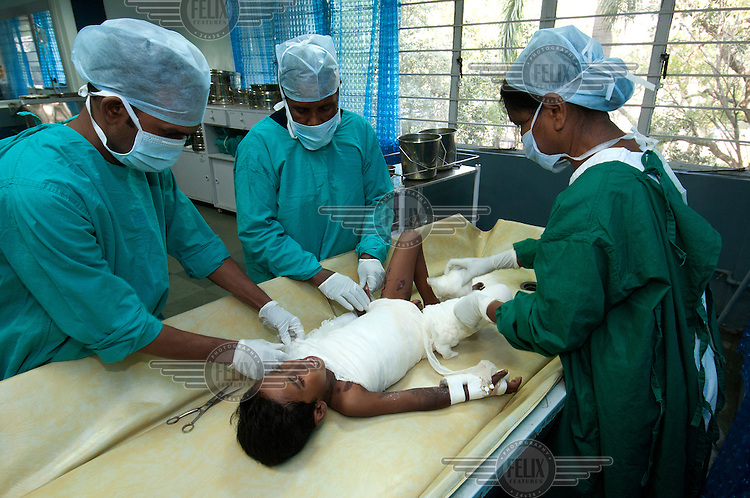 A child, who was scalded by boiling tea at his home, cries as he has his dressings changed during a painful procedure in the burns unit of the Tata Main Hospital.