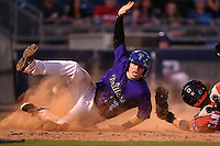 Tulsa Drillers catcher Ryan Casteel (32) slides into home past catcher Pat Cantwell (12) during the second game of a doubleheader against the Frisco Rough Riders on May 29, 2014 at ONEOK Field in Tulsa, Oklahoma.  Frisco defeated Tulsa 3-2.  (Mike Janes/Four Seam Images)