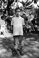 Young boy attending a friend's birthday party. Community of Nueva Esperanza, El Salvador, 1999.