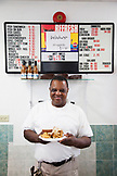 BERMUDA. St. George. Art Mel in his restaurant called Art Me's Spicy Dicy. He is holding his famous Fish Sandwich.