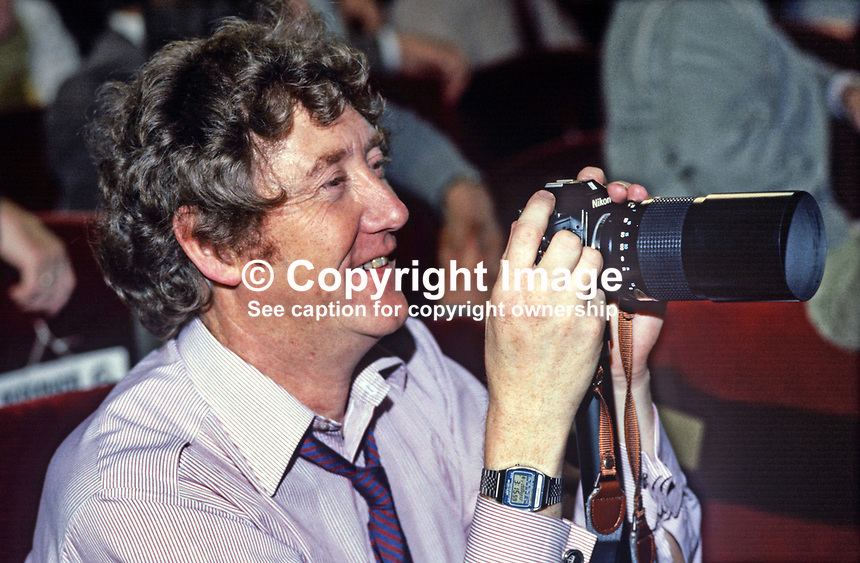 Keen amateur photographer, Austin Mitchell, MP, photographing party colleagues on the platform at Labour Party's annual conference, October, 1984, 19840122AM1<br />