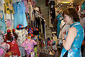 July 24, 2011 - Yokohama, Japan - An employee speaks to a customer about Chinese dresses for kids that she is selling at her shop in Yokohama's Chinatown district. Yokohama Chinatown is a largest Chinatown in Asia with a history that dates back to approximately 150 years. Until today, it still remains as a popular tourist destination for locals and travelers abroad. (Photo by Yumeto Yamazaki/AFLO)