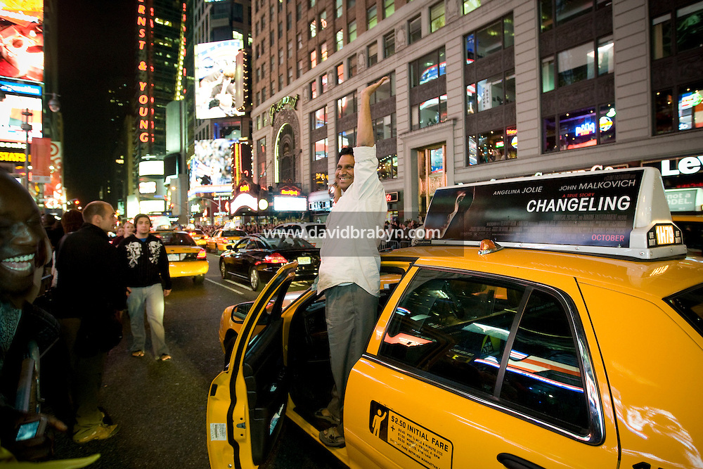 A cab driver celebrates as he drives through Times Square in New York, NY, United States, after the announcement of Barack Obama's victory in the 2008 US presidential election, 4 November 2008.