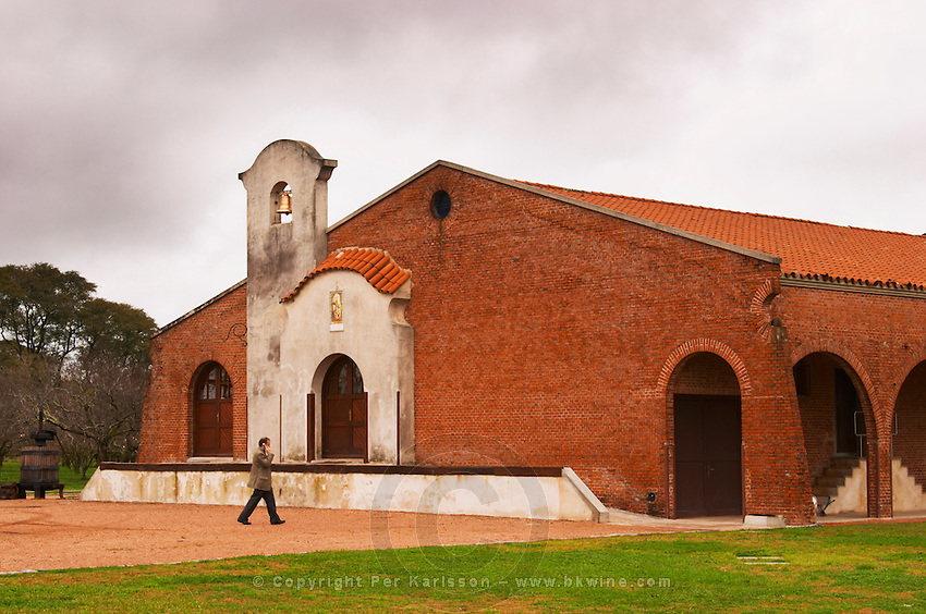 The main winery building built in colonial style. A man Juan Luis Bouza owner walking in the yard Bodega Bouza Winery, Canelones, Montevideo, Uruguay, South America