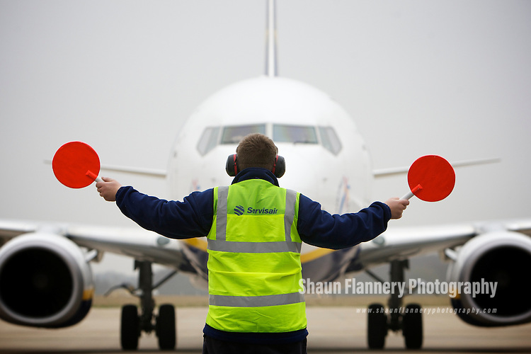 Pix: Shaun Flannery/shaunflanneryphotography.com...COPYRIGHT PICTURE>>SHAUN FLANNERY>01302-570814>>07778315553>>..17th February 2011...........Robin Hood Airport Doncaster Sheffield..Airside operations. A Ramp Agent directs Ryanair EI-EBB, Boeing 737-8AS aircraft on to the stand.
