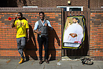 © Joel Goodman - 07973 332324 . 12/08/2017 . Manchester , UK . A portrait of Haile Selassie hanging from a gate as people gather along the route to watch the parade . The annual Caribbean Carnival J'Ouvert Parade through Moss Side in South Manchester . The 2017 theme is Bacchanal . There is concern in the community following the stabbing to death of Sait Mboob during a mass fight which saw several seriously hurt on Tuesday night (8th August 2017) . Photo credit : Joel Goodman