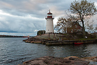 The storm clouds break up  at sunrise as a freighter passes Crossover Island Lighthouse in the St. Lawrence River in early November -1000 Islands, New York State