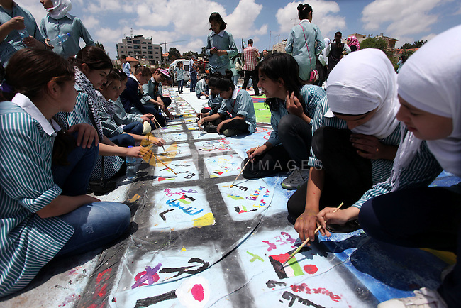 Palestinian students draw paintings to commemorate Nakba Day in the West Bank city of Ramallah in May 14, 2013. Palestinians are preparing to mark Nakba Day on May 15 which commemorates the exodus of hundreds of thousands of their kin after the establishment of Israel state in 1948. Photo by Issam Rimawi