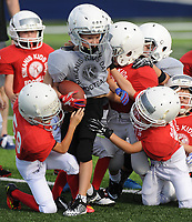 NWA Democrat-Gazette/ANDY SHUPE<br /> First- and second-grade Gray Team's Townsend Teff (center) is brought down by Red Team's Hudson Hasenbeck (left), John Baker and Landon Sabatini (right) Friday, Aug. 11, 2017, during the 64th annual Kiwanis Kids Day Football program at Wildcat Stadium at Har-Ber High School in Springdale. Visit nwadg.com/photos to see more photographs from the games.