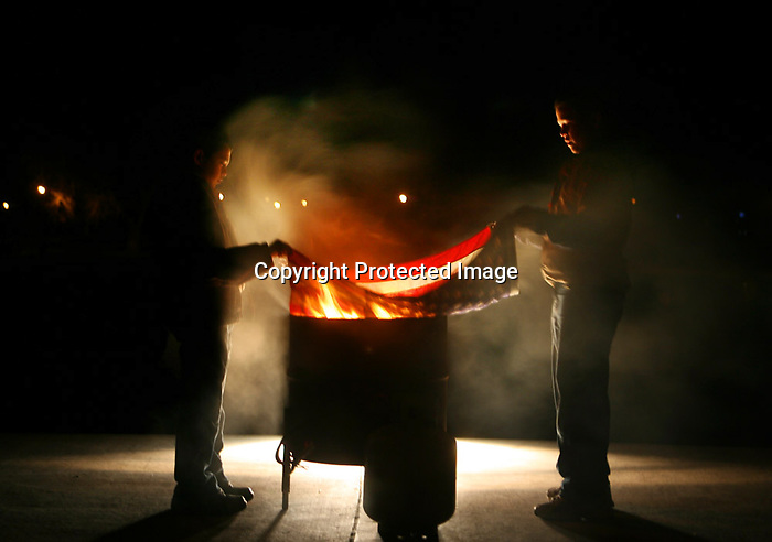 Cub scouts Zachary Trujillo, left, and Todd Wagner set an American flag into a barrel to be burned during a flag retirement ceremony at the amphitheater in Lions Park Tuesday night.  Boy scout Jeff Vossler organized the ceremony for his Eagle Scout project and featured members of Boy Scout Troop 102 and Cub Scout Troop 221. Michael Smith/staff