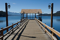 Nahuel Huapi Lake in Argentina's lake district, is famous for the speed with which it can change from benign placidity to white-capped fury. Here we see it in the first of these moods, looking out along a pier at Villa la Angostura.