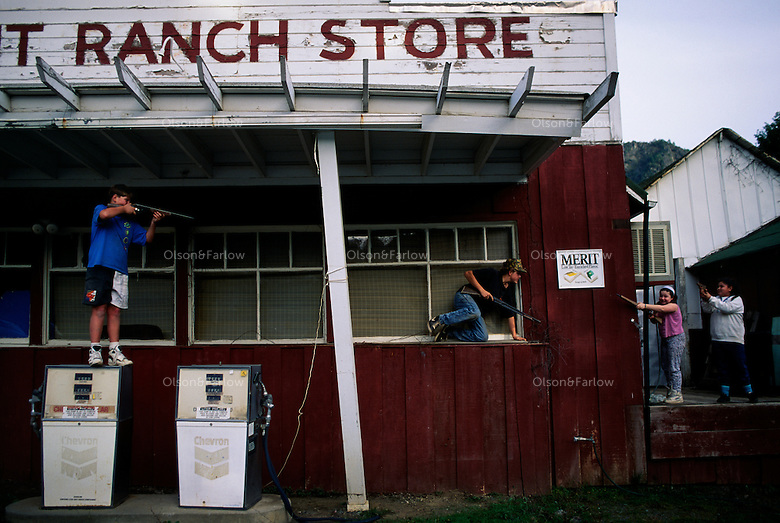"Kids play a western-style ""shoot em up"" with toy guns outside the old gas station and ranch store."