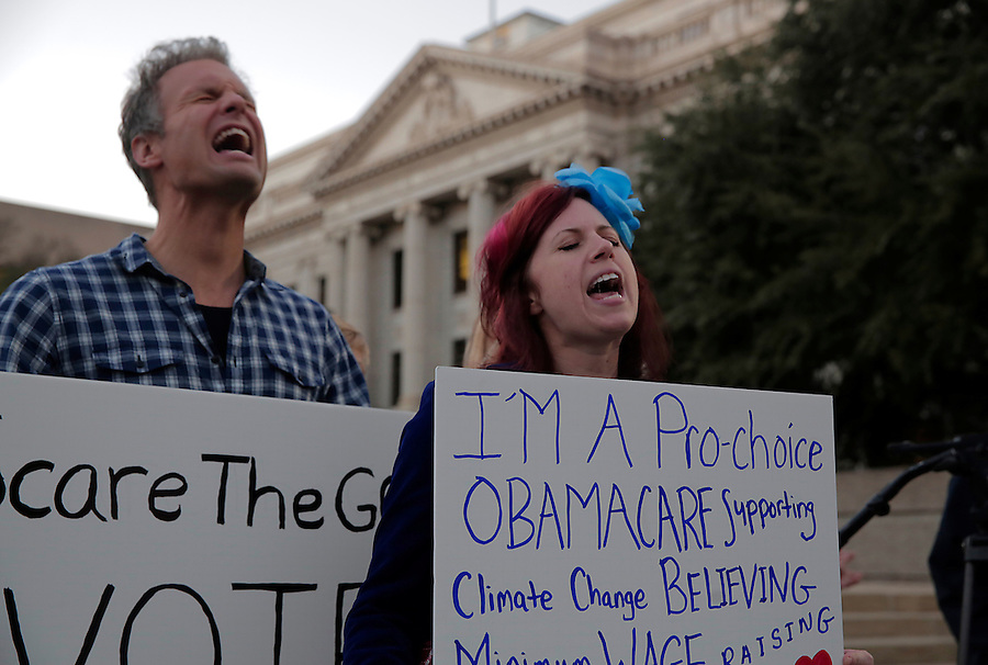 GREENSBORO, NC - NOVEMBER 3:   Evan Olson, left, and Jessica Mashburn scream their support for voter rights, and hold signs supporting Democrats, during a Moral March to the Polls event sponsored by the North Carolina NAACP in Greensboro, NC, on Monday, November 3, 2014.  (Photo by Ted Richardson/For The Washington Post)