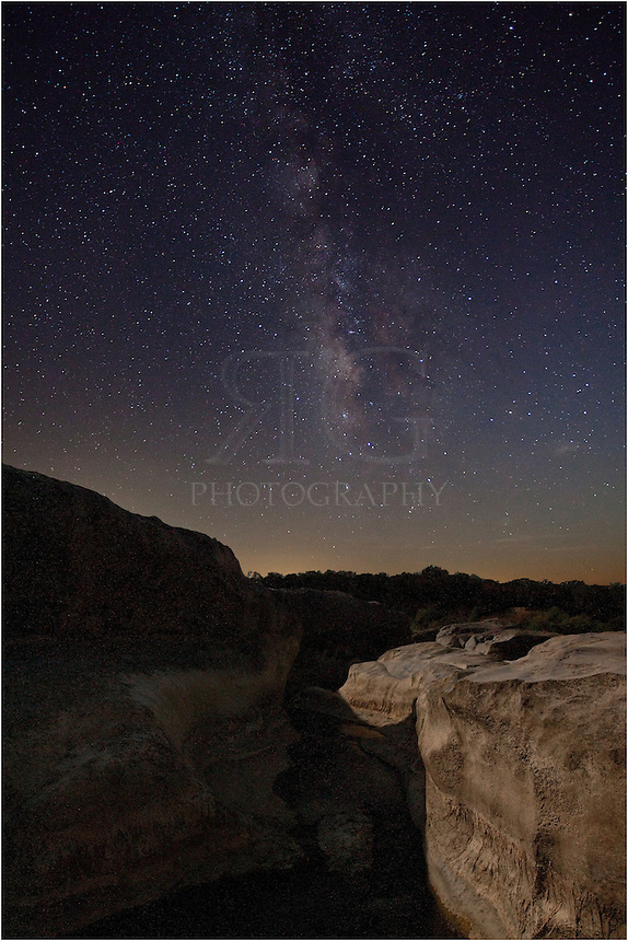 The moon was hiding as the Milky Way made its way over the Hill Country in this nighttime view of the Texas Landscape. Standing on the edge of a small canyon, I took several images of both the canyon and the overhead sky to get the exposure correct.