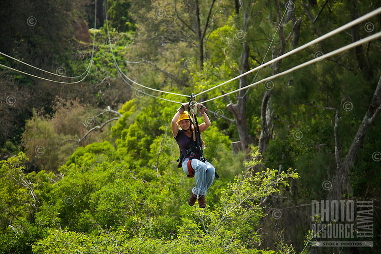 Woman flying through the canopy of trees in the rainforest while Ziplining on the Big island with Kohala zipline