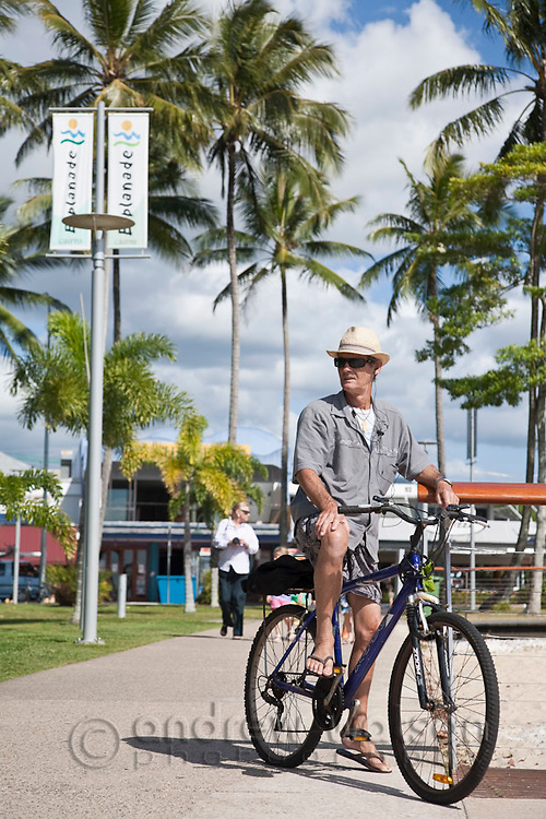 Local man cycling at the Esplanade.  Cairns, Queensland, Australia