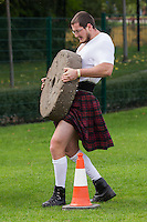 Competitor lifts a grindstone in the Highland Game competition held at the FitParade mass sports event in Budapest, Hungary on October 17, 2015. ATTILA VOLGYI