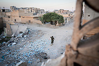 August 2017. Raqqa, Syria.<br /> A member of the MFS walks through Al-Nahda neighbourhood on the western front lines of Raqqa, Syria.<br /> The MFS (Syriac Military Council) are a group of Assyrian Christians who fight alongside the Syrian Democratic Forces in the fight to topple ISIS.<br /> Photographer: Rick Findler