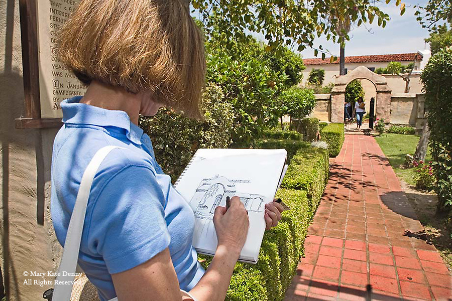 Young woman student draws Spanish style gate at San Gabriel Mission, California on field trip to inform architectural landscape design of what makes it sacred