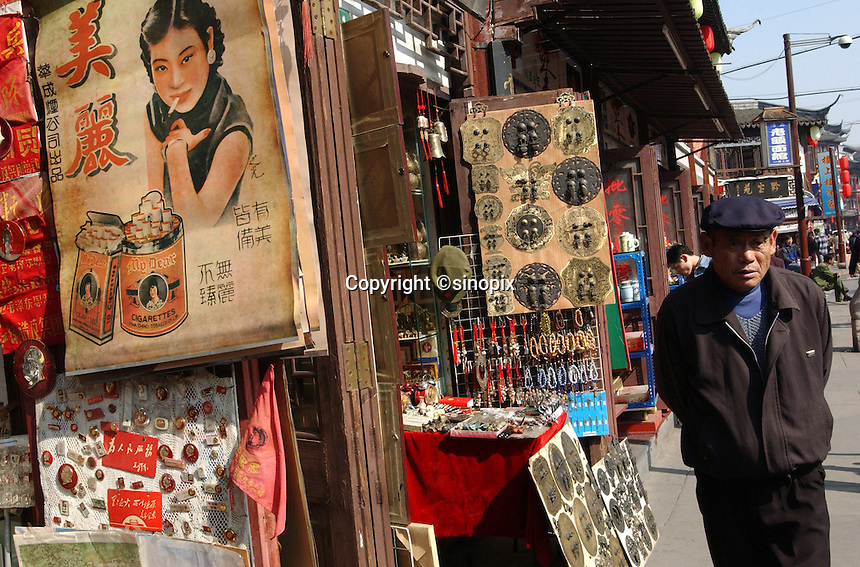 A shop selling antiques from the first half of the 20th century in Shanghai, China. Their items are mostly old posters advertising various commodities such a cigarettes and also of Chairman Mao's image. .13-NOV-03