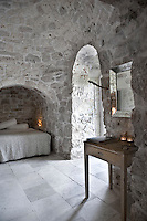 The small table and bevelled mirror in this bedroom are flea market finds, and add to the simple, rustic charm of the medieval room