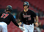 BOSTON, MA - APRIL 17: UMass' Anthony Videtto, right, is congratulated by teammate Kane Medina after scoring a game tying run against Harvard in the third inning during the 30th Annual Baseball Beanpot Championship Game at Fenway Park in Boston, Massachusetts on April 17, 2019. Photo by Christopher Evans