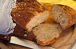 A loaf of wholemeal cereal bread on a wooden bread board with a bread knife