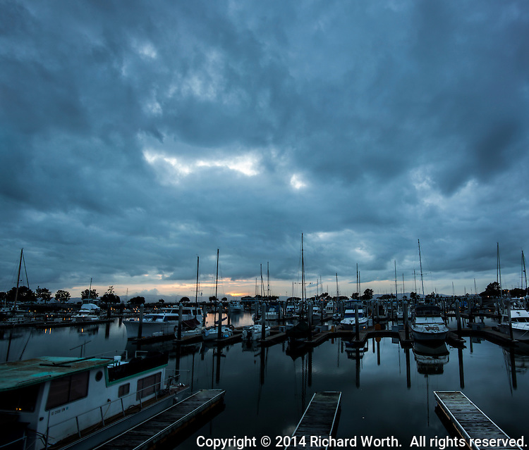 The sky over boats moored at the San Leandro Marina roll heavily with dark, foreboding clouds, but they only threaten, never deliver.  Not yet.  Not now.  It's a break in the storms.
