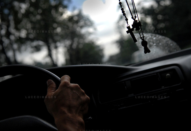 A crucifix hangs in a cab driver's window in Manila, Philippines..**For more information contact Kevin German at kevin@kevingerman.com