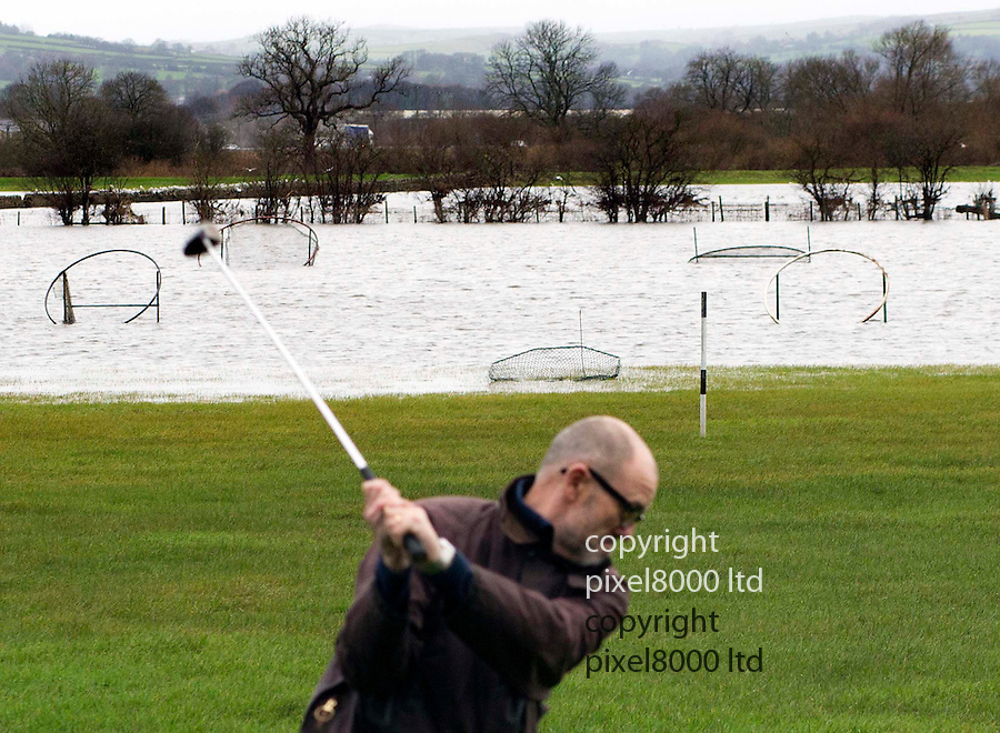 """Pic shows: Flooding in Yorkshire.<br /> A brave local golfer gets some last chance practice in before the arrival of Storm Frank.<br /> Silsden Golf Range was still open for business but the local owner admitted it was taking """"quite a bit longer"""" to get the balls back from the totally submerged targets baskets.<br /> <br /> <br /> <br /> Pic by Gavin Rodgers/Pixel 8000 Ltd"""