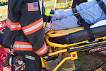 Emergency Medical Technicians EMTs and firefighters help a patient on a stretcher