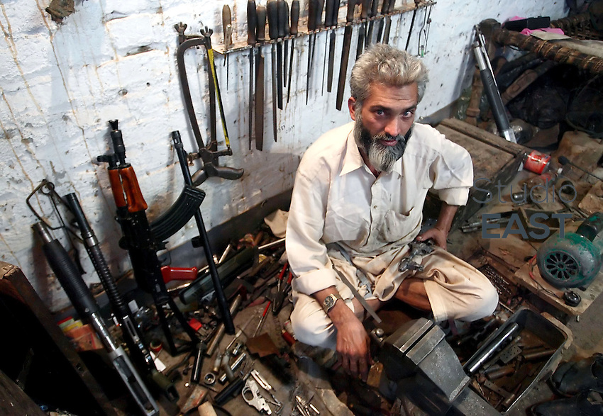 A gunsmith sits among the tools of his trade in his workshop in Pakistan's most prominent arms producing village of Darra Adam Khel, Pakistan, Thursday, October 19, 2006. Darra is a dusty, Wild West-type town, crawling with intelligence agencies, drug smugglers and gun-toting Pathan tribesmen. Darra-built Kalashnikovs, not known for their durability, sell for US$30 to US$45 alongside knuckledusters, shotguns with telescopic sights and twelve bores made to look like M16 assault rifles. Much of the weaponry is made from scrap metal from shipyards. Pakistan's government's attempts to regulate the Darra weapon industry always ended in failure. Photo by Simon Lim/Pictobank.