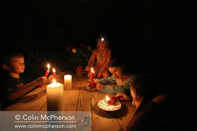 A group of children lighting candles during a power cut at their home in Capel Curig in north Wales. The electricity supply was disrupted by high winds and heavy storms which brought power lines down across the country. The village lay within the Snowdonia National Park, a conservation area which was designated as protected against development.