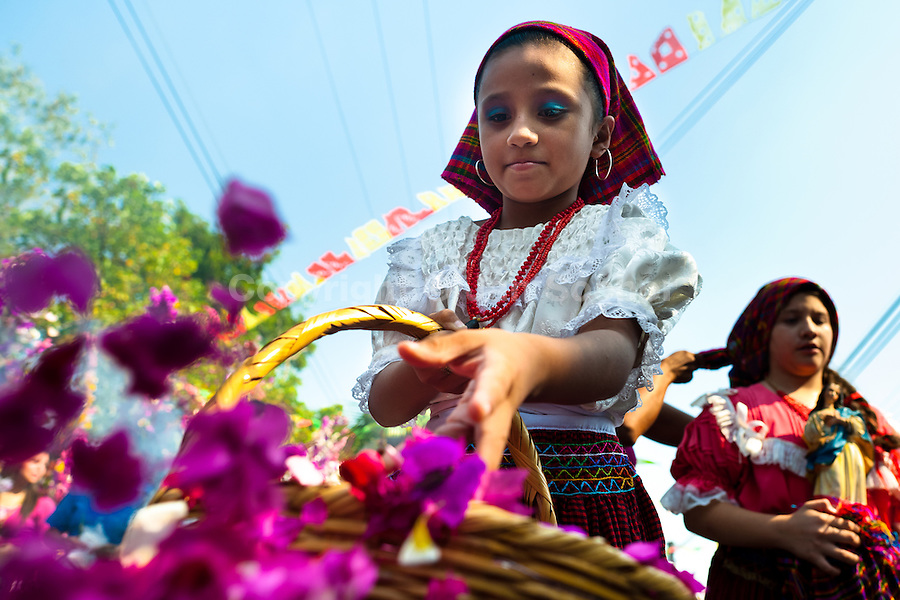 "A Salvadoran girl throws colorful flower blooms during the procession of the Flower & Palm Festival in Panchimalco, El Salvador, 8 May 2011. On the first Sunday of May, the small town of Panchimalco, lying close to San Salvador, celebrates its two patron saints with a spectacular festivity, known as ""Fiesta de las Flores y Palmas"". The origin of this event comes from pre-Columbian Maya culture and used to commemorate the start of the rainy season. Women strip the palm branches and skewer flower blooms on them to create large colorful decoration. In the afternoon procession, lead by a male dance group performing a religious dance-drama inspired by the Spanish Reconquest, large altars adorned with flowers are slowly carried by women, dressed in typical costumes, through the steep streets of the town."