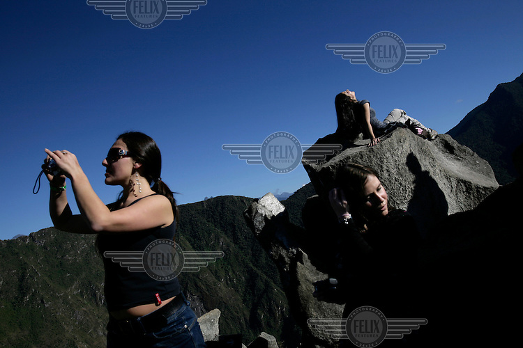 Female tourists take photos and sunbathe on the Huayna Picchu (Wayna Picchu), a site high above Machu Picchu, the so-called 'Lost City of the Incas'. Each day hundreds of tourists wait outside of the ruins of Machu Picchu but only the first 400 people to arrive at the site get to climb to Huayna Picchu..