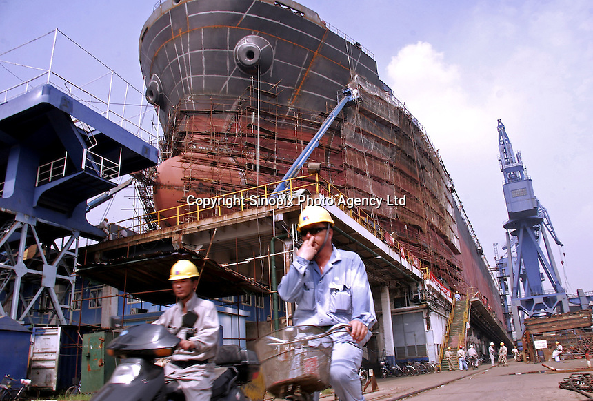 Chinese workers on bicycles ride past a ship under construction at the Hudong Zhonghua Shipbuilding Co., LTD in Shanghai, China. China is the world's third largest shipbuilding nation after South Korea and Japan. While growing international interest in its lower building cost and domestic tanker demand to fulfill the country's hunger for energy is likely to push the country to the top position, the rapidly increasing price of steel has also undercut the industry's profitability..