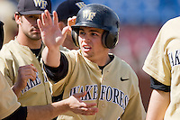 Bentley Heyman #8 of the Wake Forest Demon Deacons is congratulated by teammates after scoring a run against the Xavier Musketeers at Wake Forest Baseball Park March 7, 2010, in Winston-Salem, North Carolina.  Photo by Brian Westerholt / Four Seam Images